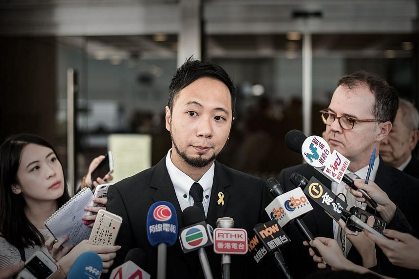 Political activist Ken Tsang talks to the media outside the high court of justice in Hong Kong on April 17, 2015.