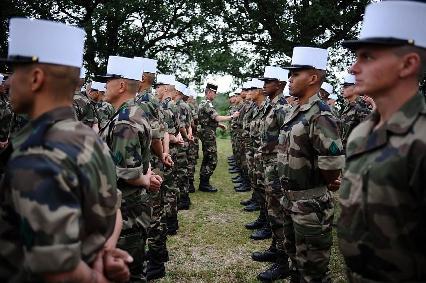 Soldiers of the French Foreign Legion standing at attention while receiving their white kepi.