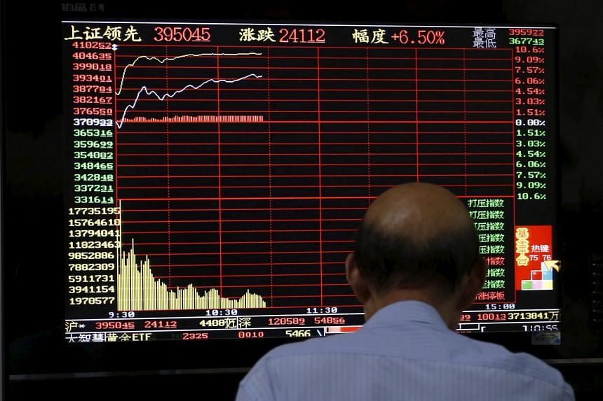 An investor looks at a computer screen showing stock information at a brokerage house in Shanghai, China. Singapore stocks were in positive territory on Monday riding the wave of a possible Greece deal and steady China markets.  PHOTO: REUTERS