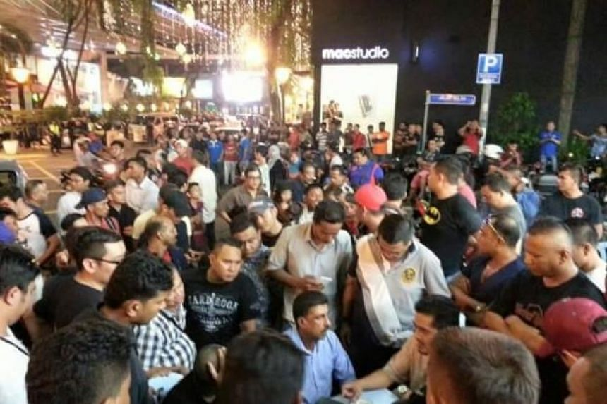 Police speaking to protesters outside Low Yat Plaza in Kuala Lumpur on Sunday night.