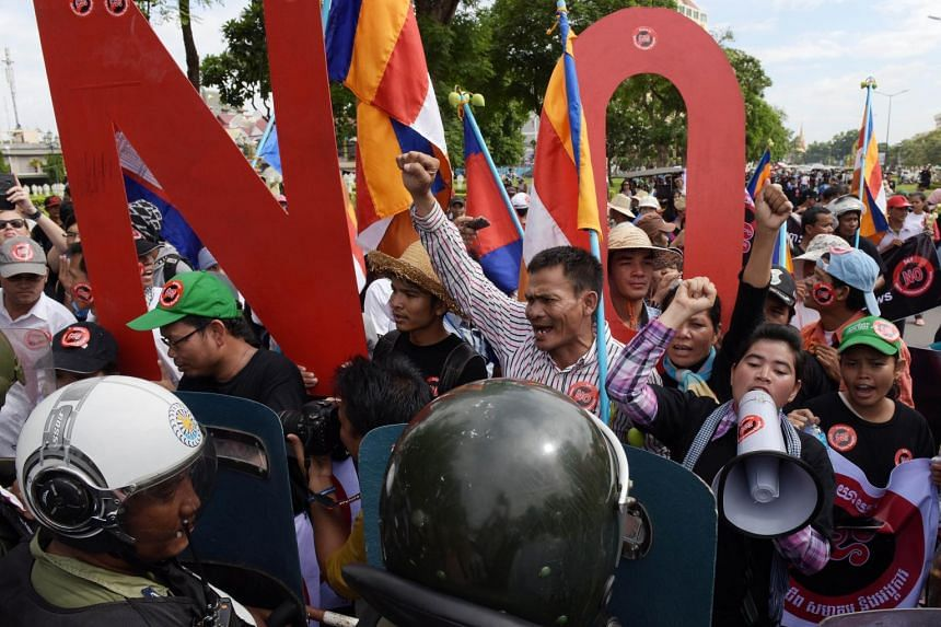 Cambodian protesters face off with police as they shout slogans during a protest near the National Assembly in Phnom Penh on July 13, 2015.