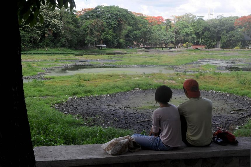 A Filipino couple watches the cracked bottom of a dried lake in a park in a suburb of Manila on June 6, 2015.