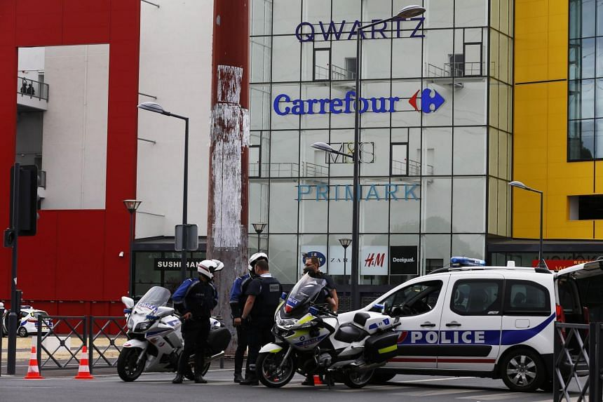 Police officers stand outside the Qwartz mall in Villeneuve-La-Garenne after a robbery attempt on July 13, 2015.