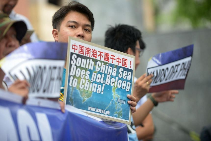 Protesters brandish placards at a rally in front of the Chinese Consulate in Manila's financial district on July 7, 2015.