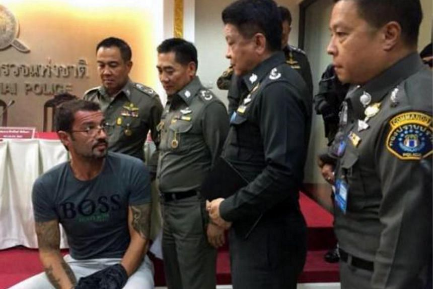 Xavier Justo (seated), after being arrested in Thailand for allegedly leaking information about PetroSaudi International.