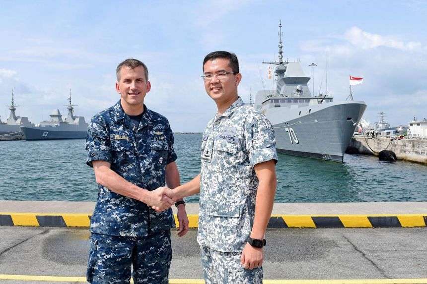 US Navy Rear Admiral Charles Williams (left) with Singapore's Rear Admiral Lew Chuen Hong as part of the opening ceremony for the annual Cooperation Afloat Readiness and Training (CARAT) joint-naval exercise in Singapore on July 13, 2015.