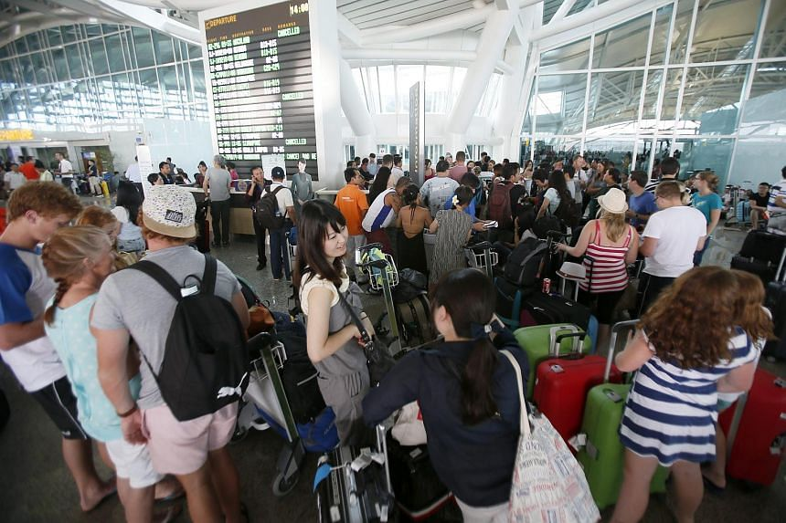 Passengers wait for their delayed flights at Bali's Ngurah Rai International Airport in Bali, Indonesia, on July 12, 2015.