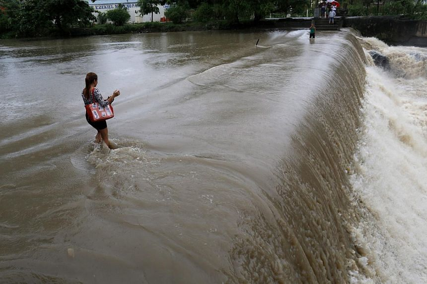Filipinos cross a swelling river in Las Pinas city, south of Manila, Philippines, on July 9, 2015.