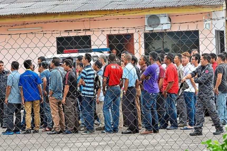 Some of the accused queueing to enter the special Sessions Court at the Pekan Nenas detention centre for illegals in Pontian, Johor.