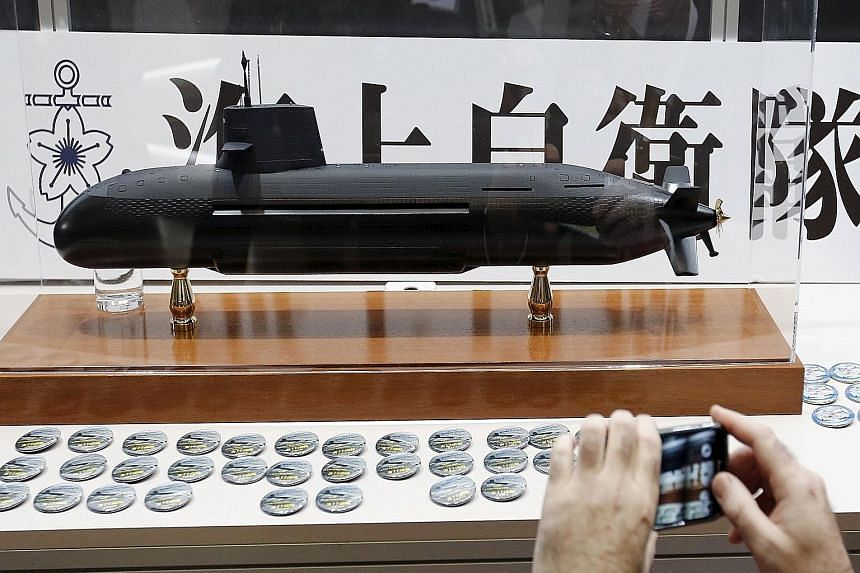 A visitor taking a photograph of a Soryu submarine model at an exhibition in Yokohama in May. Organisers said it was the first military industry trade show in Japan, and the first anywhere to feature Japanese manufacturers.