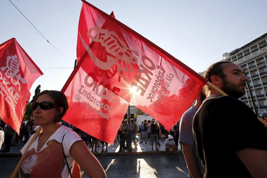 Anti-EU protesters holding flags during a demonstration in front of the parliament building in Athens.