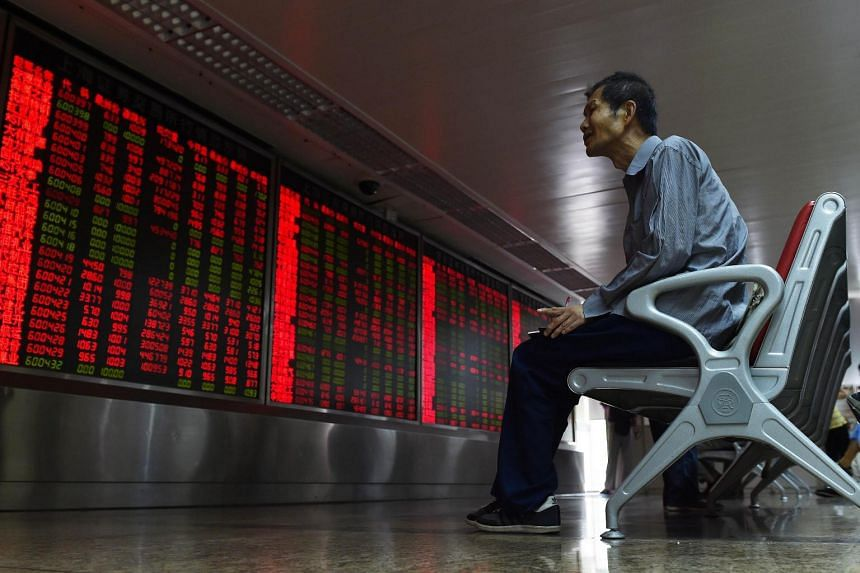 An investor looking at a board showing stock market movements at a securities company in Beijing.