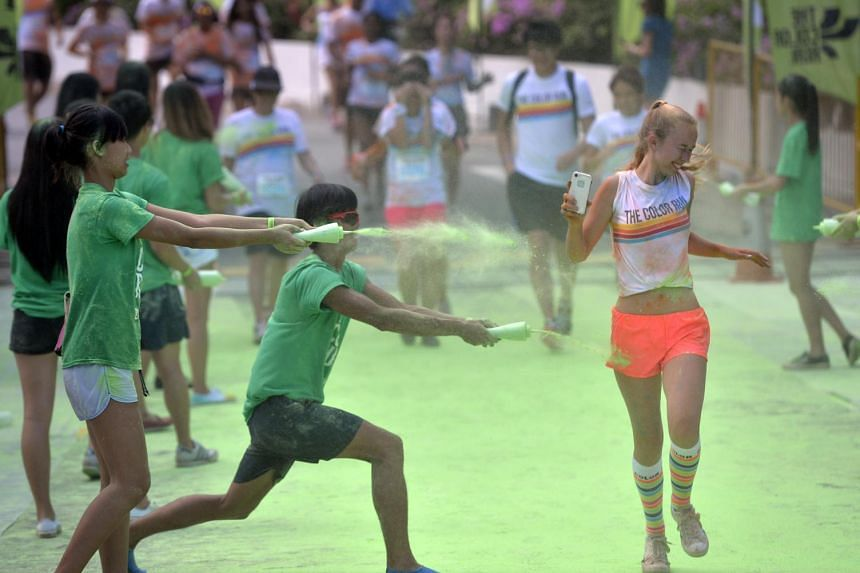 A participant getting splashed with green-coloured powder during the Colour Run held on Aug 30, 2014.