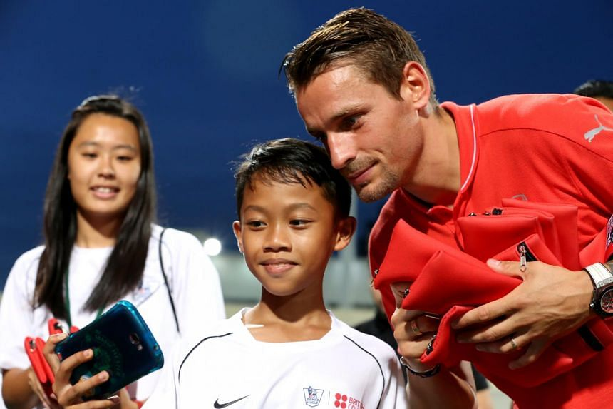 Mathieu Debuchy taking a selfie with a young fan at the Premier Skills festival at Jalan Besar Stadium on July 14, 2015.