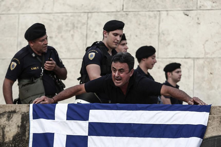 A protester holding a Greek flag outside the parliament in Athens.