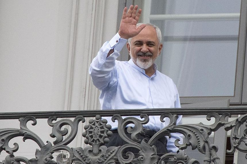 Iranian Foreign Minister Mohammad Javad Zarif waving from a balcony of the Palais Coburg Hotel where nuclear talks are being held in Vienna.