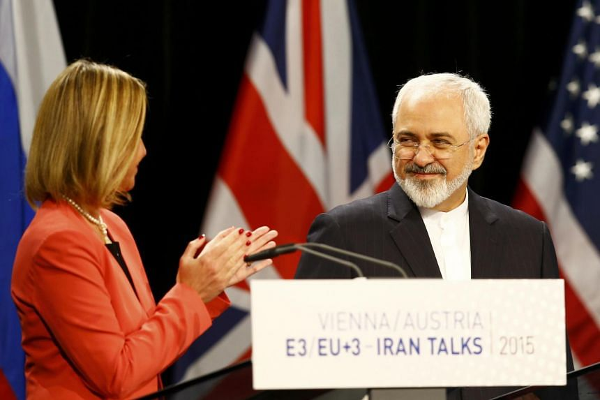 High Representative of the European Union for Foreign Affairs and Security Policy Federica Mogherini (left) applauds Iranian Foreign Minister Mohammad Javad Zarif during a joint news conference after a plenary session at the United Nations building i