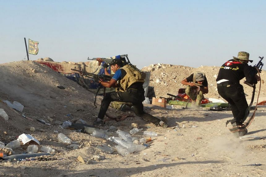 Iraqi security forces firing their weapons during clashes with Islamic State militants on the outskirts of Ramadi.