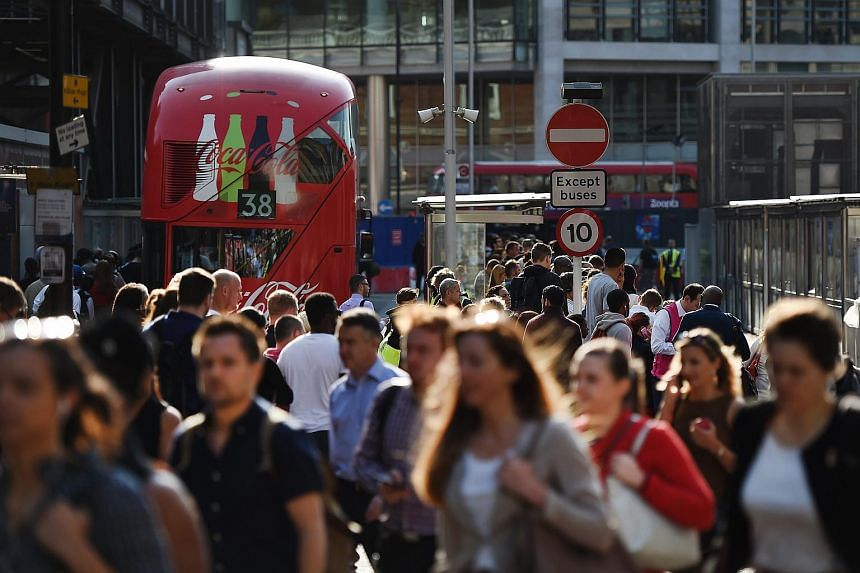 Commuters queueing for buses at Victoria Station in London.