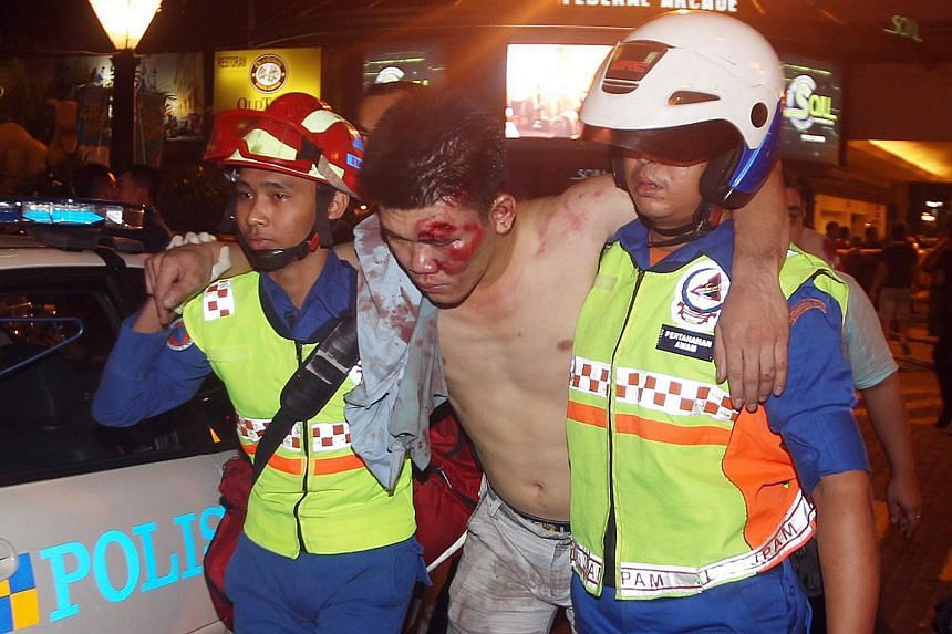 Police escorting an injured man after the riot at Low Yat Plaza.