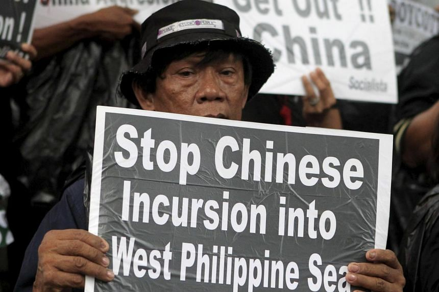 A protester holds a placard during a rally over the South China Sea disputes with China, outside the Chinese Consulate in Makati City, Metro Manila on July 10, 2015.