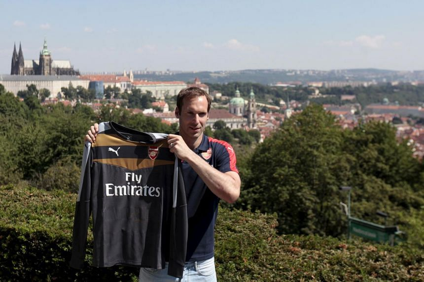 Czech soccer player Petr Cech shows his Arsenal jersey during his presentation in Prague on July 1, 2015.