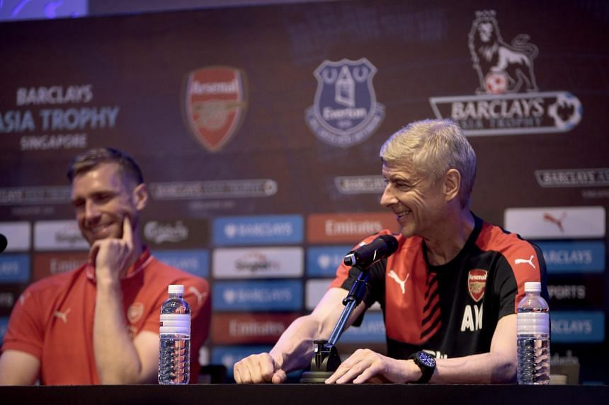 English Premier League club defender Per Mertesacker (left) and manager Arsene Wenger (right) speak to journalists at a press conference ahead of the Barclays Asia Trophy soccer tournament in Singapore, on July 14, 2015.