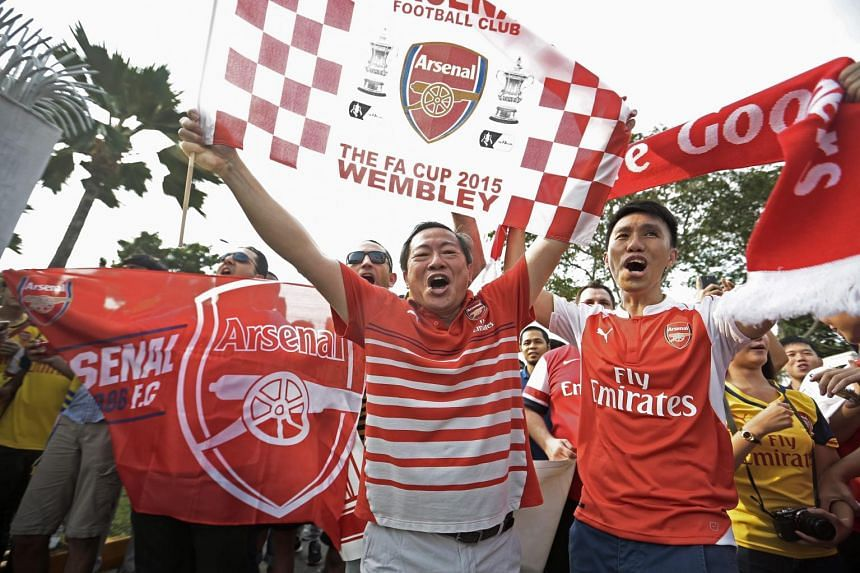 Fans of Arsenal Football Club hold up scarves and flags as they wait for the team outside a terminal at the Changi Airport ahead of the Barclays Asia Trophy tournament in Singapore, on July 13, 2015.