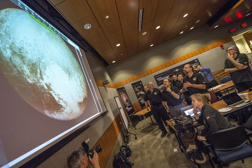 A handout picture made available by Nasa shows members of the New Horizons science team reacting to seeing the spacecraft's last and sharpest image of Pluto before closest approach later in the day, at the Johns Hopkins University Applied Physics Lab