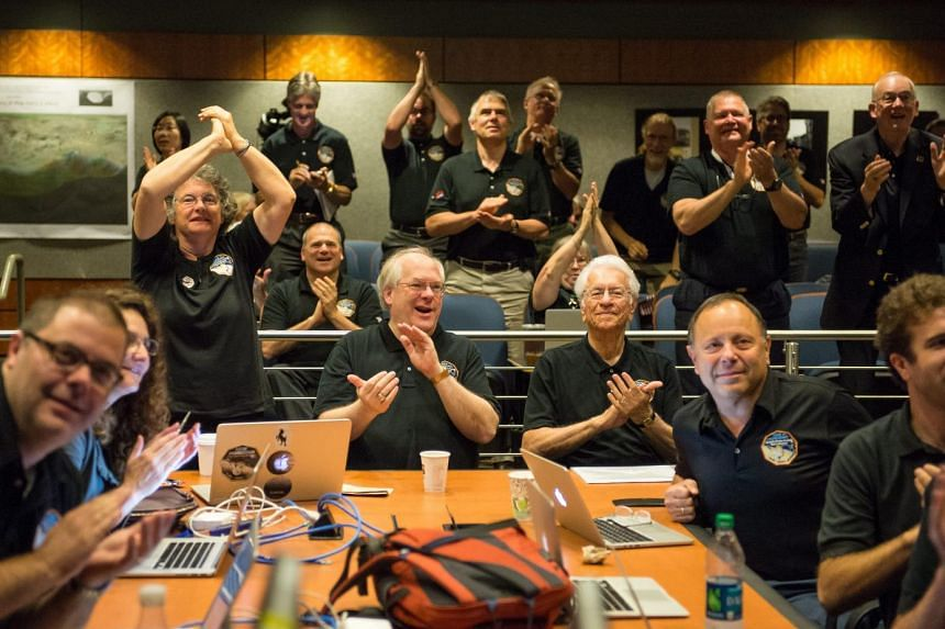 A handout image dated on July 14, 2015 and made available by Nasa, showing Members of the New Horizons science team react to seeing the spacecraft's last and sharpest image of Pluto before closest approach later in the day, on July 14, 2015 at the Jo
