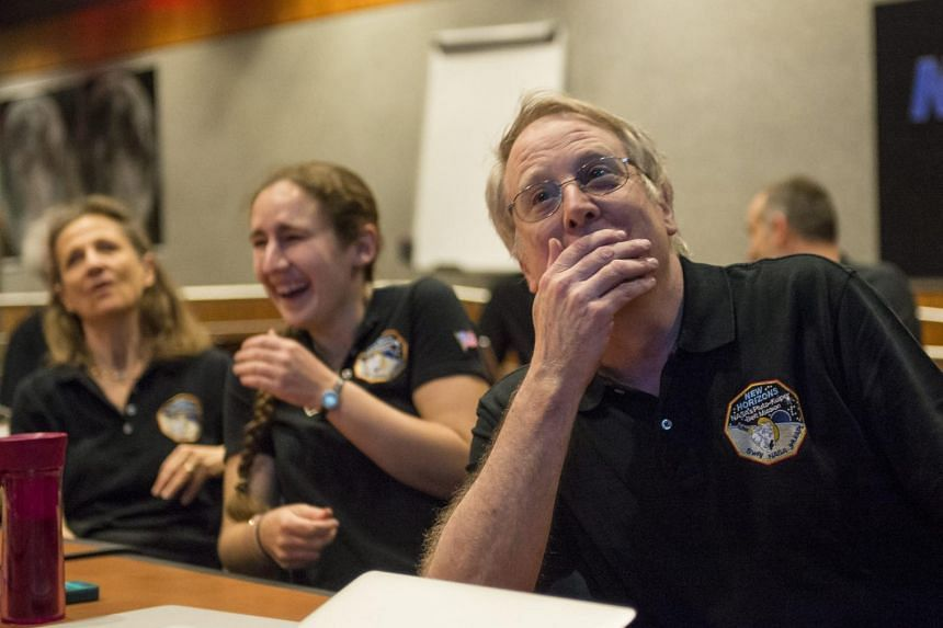 A handout image dated on July 14, 2015 and made available by Nasa, showing Members of the New Horizons science team react to seeing the spacecraft's last and sharpest image of Pluto before closest approach later in the day, Tuesday, on July 14, 2015