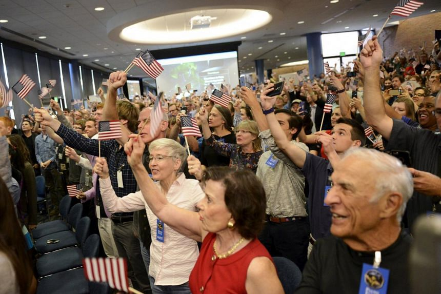 Scientists and guests cheer at the countdown as the spacecraft New Horizons approaches a flyby of Pluto, at Nasa's Johns Hopkins Applied Physics Laboratory in Laurel, Maryland, on July 14, 2015.