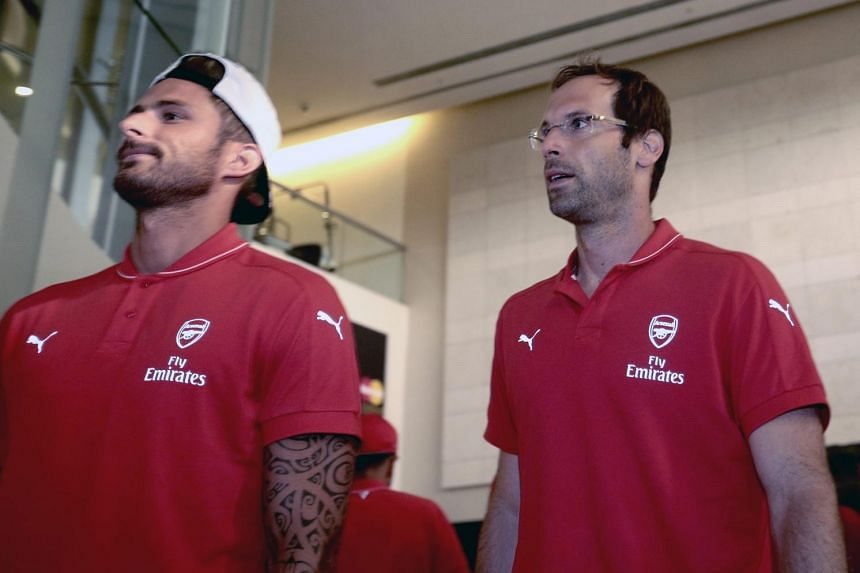 Arsenal forward Olivier Giroud (left) and goalkeeper Petr Cech (right) arrive at the Changi Airport ahead of the Barclays Asia Trophy tournament in Singapore, on July 13, 2015.
