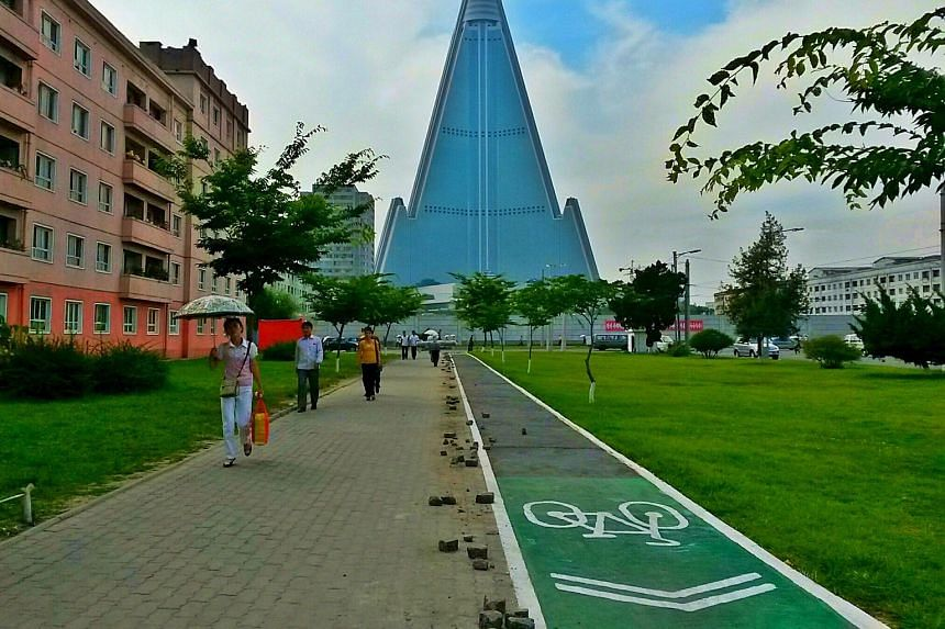 A cycle path in Pyongyang with the 105-storey Ryugyong Hotel in the background.