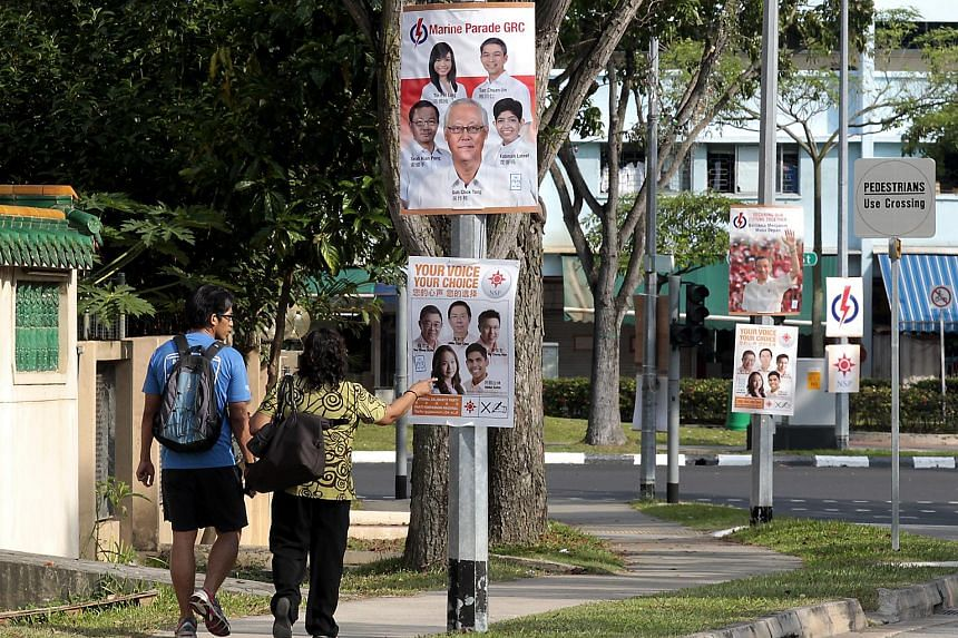 A pedestrian points at National Solidarity Party's (NSP) candidate Nicole Seah on a campaign poster at Chai Chee during the General Elections in 2011.