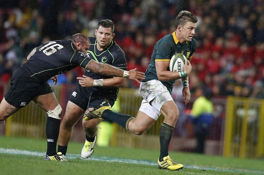 Handre Pollard of South Africa (right) breaking through a tackle from David Roumieu of France playing for the World XV (left) in Cape Town on July 11.