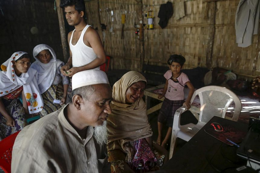 Rohingya Muslims speak to relatives from Malaysia in a refugee camp outside Sittwe, on June 2, 2015.