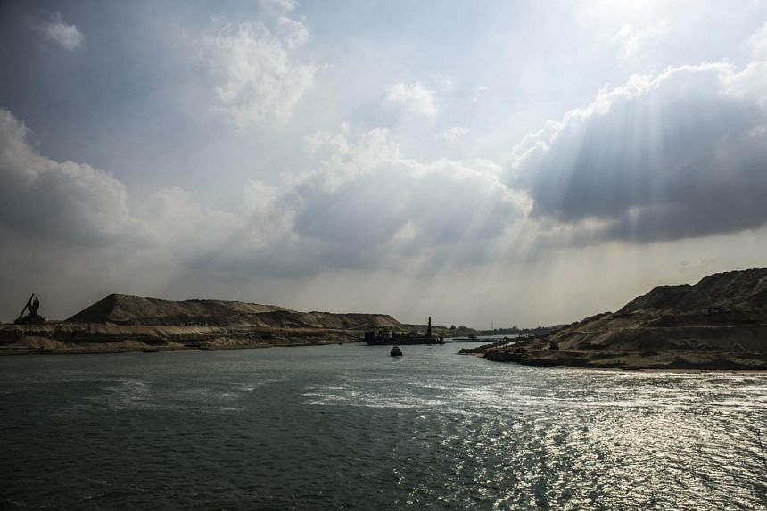 A dredger working on the new waterway of the Suez Canal near the port city of Ismailia, east of the capital Cairo, yesterday. Egypt is expanding the canal to boost its capacity and reduce transit times of ships travelling from Europe to Asia. The gov