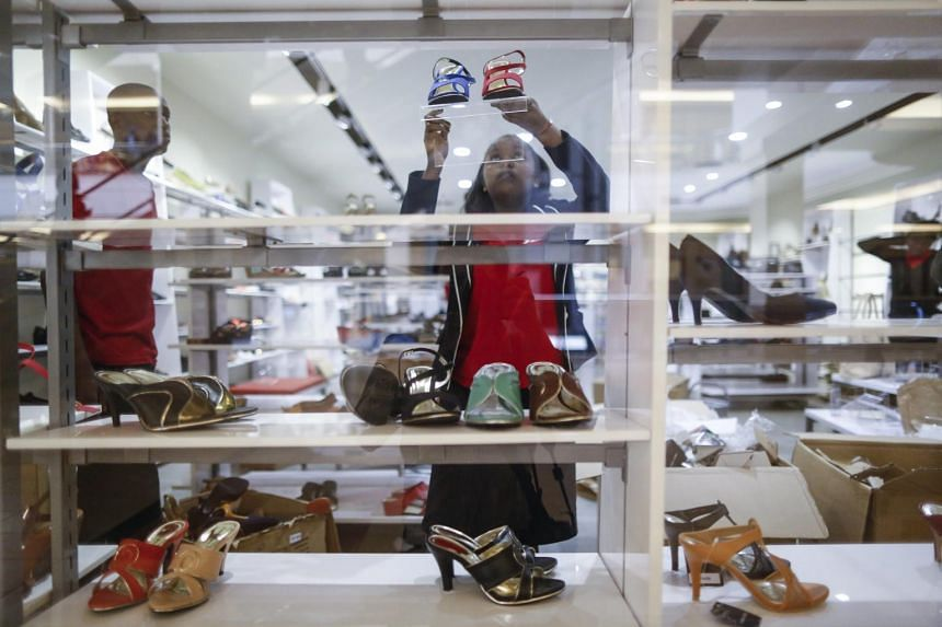 An employee puts shoes on display ahead of the mall's reopening.