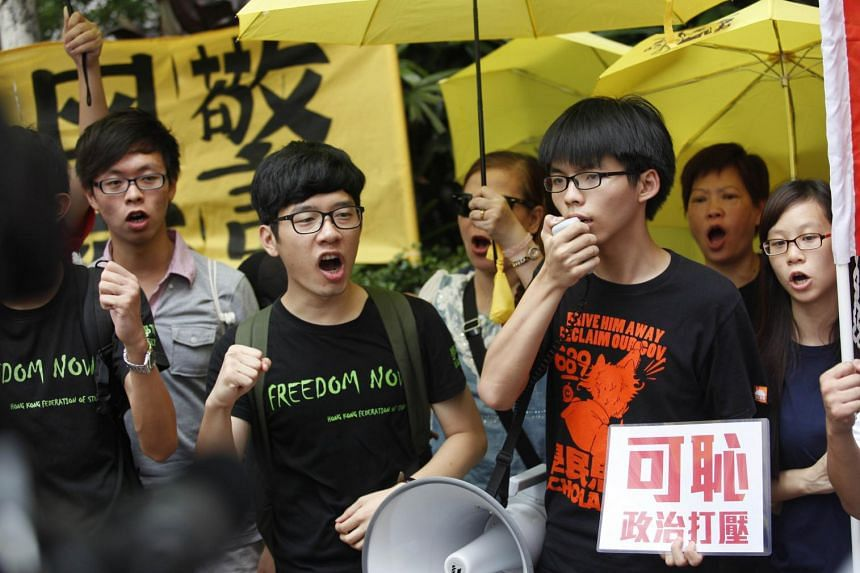 Nathan Law and Joshua Wong (right) speak to the press outside the Western District police station in Hong Kong on July 14, 2015.