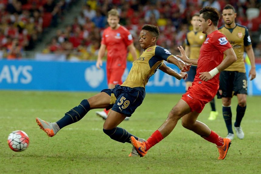 Arsenal's Chris Willock (left) and Zulfahmi Arifin go for the ball during their Barclays Asia Trophy match at the National Stadium on July 15, 2015.