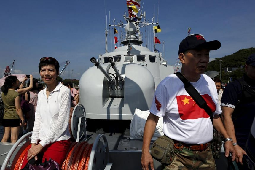 Visitors walk on a naval ship at a People's Liberation Army naval base in Hong Kong on July 1, 2015. China has arrested four defence workers for selling military secrets to foreign intelligence services.