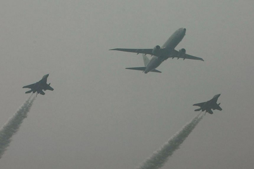 An Indian Navy Boeing P-8I Poseidon aircraft (centre) flies in formation with Indian Navy MiG-29K fighters during a flypast for the country's Republic Day Parade in New Delhi, on January 26, 2015.