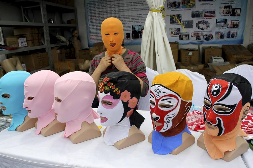 Ms Zhang Shifan tries on a face-kini mask as she demonstrates her products at an exhibition in Qingdao, Shandong province, China, on May 22, 2015.