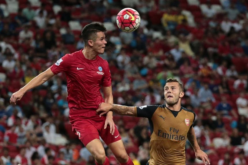 Singapore's Baihakki Khaizan heads the ball while under pressure from Arsenal's Jack Wilshere during their Barclays Asia Trophy match at the National Stadium on July 15, 2015.