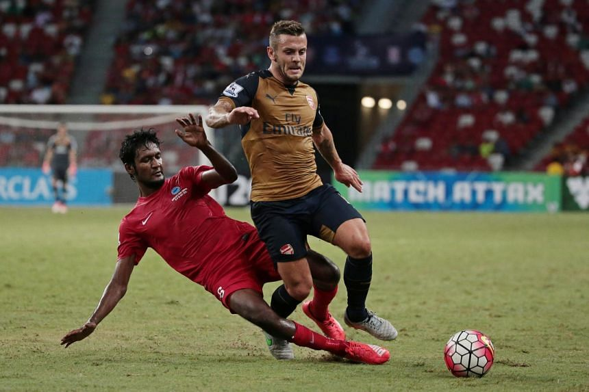 Singapore's Madhu Mohana fights for the ball with Arsenal's Jack Wilshere during their Barclays Asia Trophy match at the National Stadium on July 15, 2015.