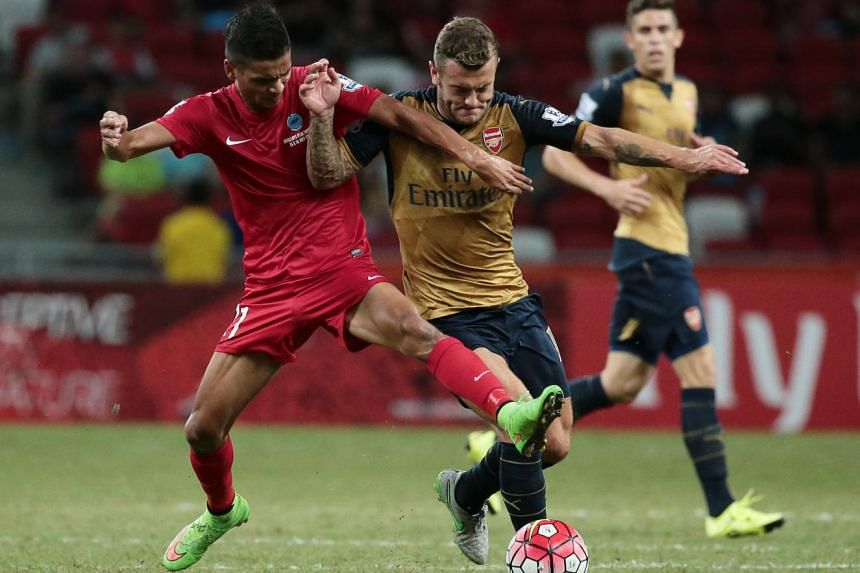 Arsenal's Jack Wilshere and Singapore's Safuwan Baharudin fight for control of the ball during their Barclays Asia Trophy match at the National Stadium on July 15, 2015.