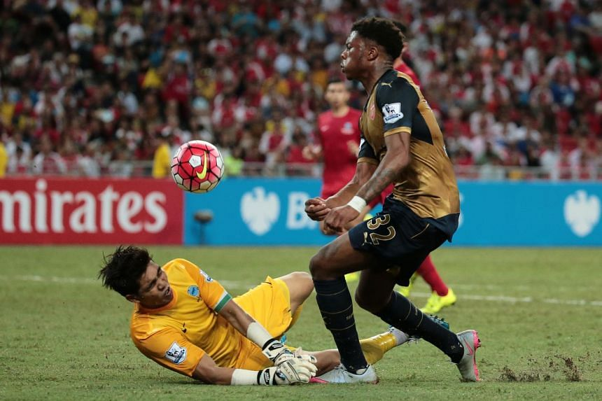 Singapore goalkeeper Izwan Mahbud defending against Arsenal's Chuba Akpom during their Barclays Asia Trophy match at the National Stadium on July 15, 2015.