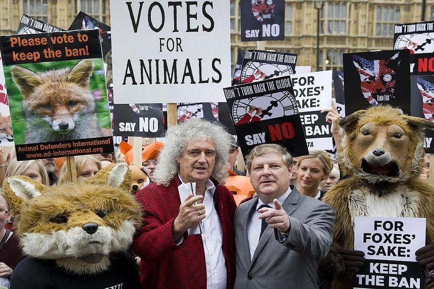 Queen guitarist Brian May (left) and Scottish National Party MP Angus Robertson at an anti-fox hunting rally in London yesterday. The British government has been forced into a dramatic climbdown after its plans to relax a ban on fox hunting were supp