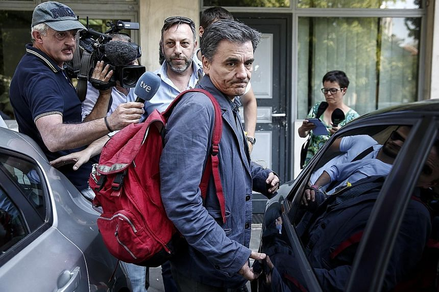 Greek Finance Minister Euclid Tsakalotos leaving after a meeting at the Syriza party headquarters in Athens yesterday. The ruling party and its junior coalition ally held meetings to prepare for Parliament sittings to pass laws which include plans fo